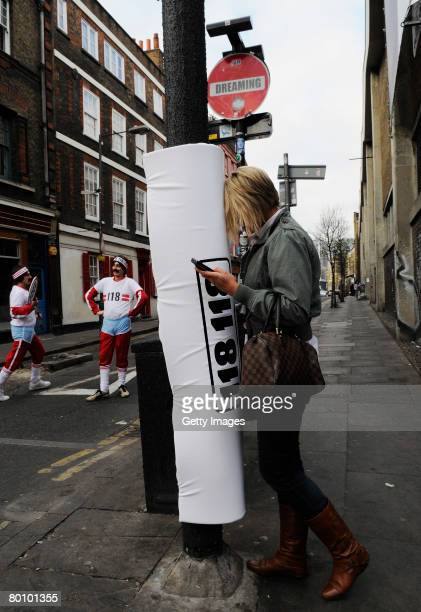 In this photo illustration a pedestrian walks into a padded lamp post whilst texting in Brick Lane on March 4 2008 in London England Brick Lane has...