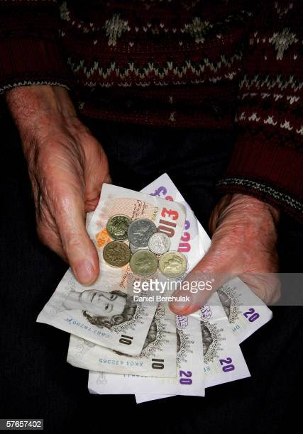 In this photo illustration a pensioner holds GBP8425 in their hand the equivalent of 1 weeks pension based on your own your late husbands wifes or...