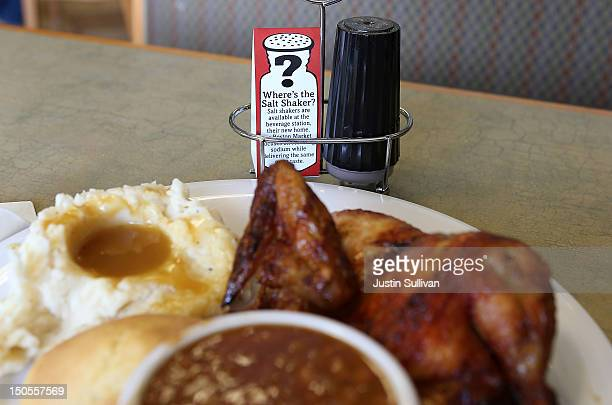 In this photo illustration A sign explaining the absence of salt shakers is posted on a table inside a Boston Market restaurant on August 21 2012 in...