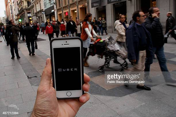 In this Photo Illustration a smart phone displays a picture with the logo of the news taxi app 'Uber' as people walk past on October 14 2014 in...
