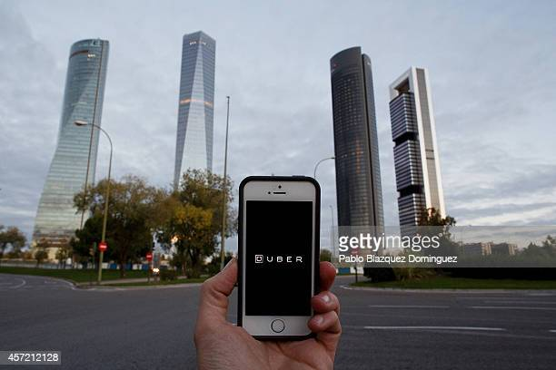 In this Photo Illustration a smart phone displays a picture with the logo of the news taxi app 'Uber' near the Cuatro Torres 'Four Towers' business...