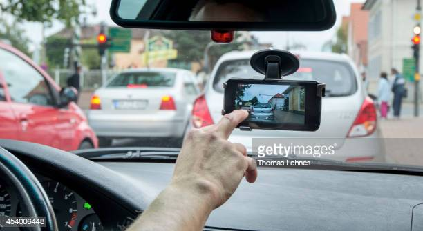 In this photo illustration a smartphone with the video app hangs attached inside the windshield of a car on August 23 2014 in Darmstadt Germany A...