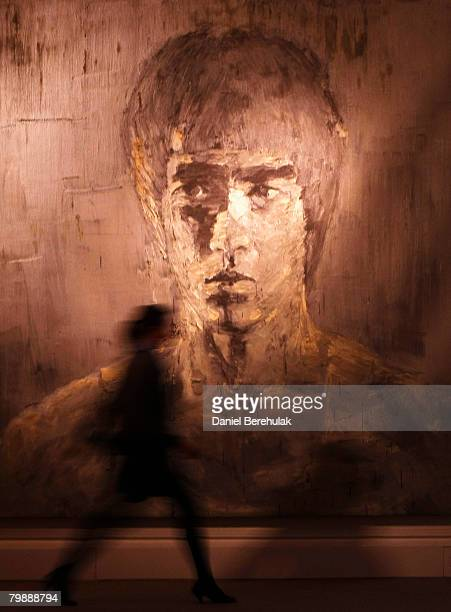 In this photo illustration a Sotheby's employe walks past a piece by Yan PeiMing called silver Bruce Lee during a press preview for Sotheby's Evening...