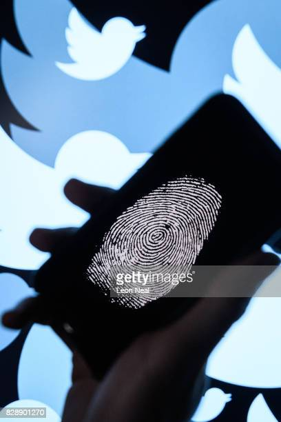 In this photo illustration a thumbprint is displayed on a mobile phone as the logo for the Twitter social media network is projected onto a screen on...