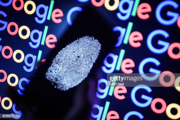 In this photo illustration A thumbprint is displayed on a mobile phone while the Google logo is displayed on a computer monitor on August 09 2017 in...