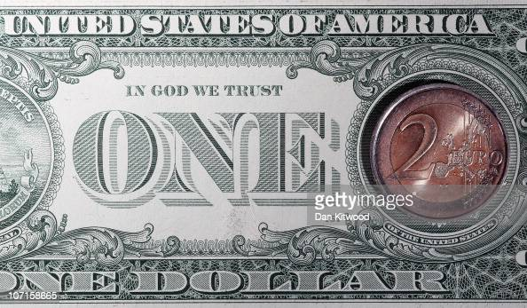 In this photo illustration a two Euro coin rest on top of a Dollar note on November 26 2010 in London England Concerns over the Euro zone debts have...