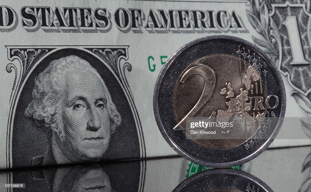 In this photo illustration a two Euro coin stands in front of a Dollar note on November 26 2010 in London England Concerns over the Euro zone debts...