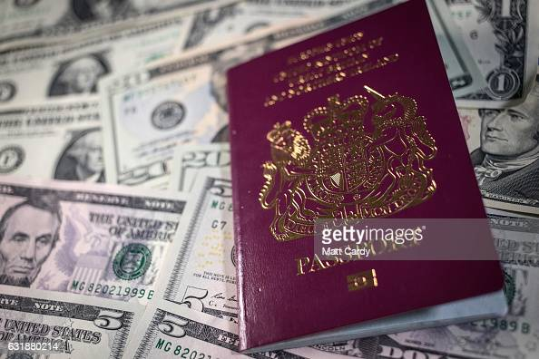 In this photo illustration a UK passport is seen besides US Dollar bills on January 17 2017 in Bristol England Sterling has dropped sharply following...