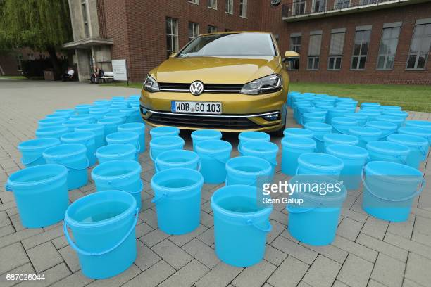 In this photo illustration a Volkswagen Golf car stands next to 114 buckets each filled 10 liters of water at the Volkswagen car factory on May 19...