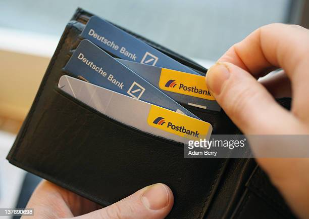 In this photo illustration a wallet holds Deutsche Bank and Postbank ATM cards taken on January 24 2012 in Berlin Germany In November 2010 Deutsche...