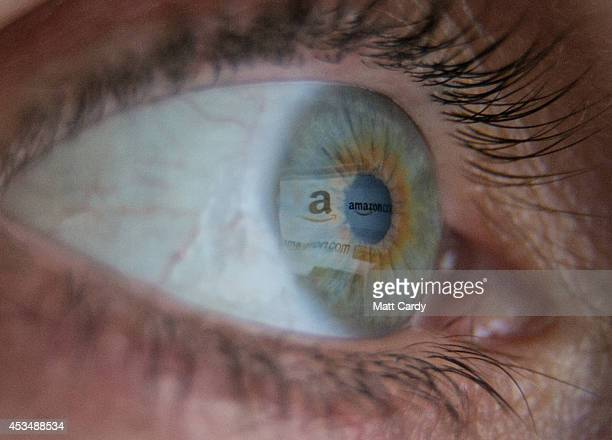 In this photo illustration a woman has the online retailer Amazon logo reflected in her eye as she shops online on August 11 2014 in Bristol United...