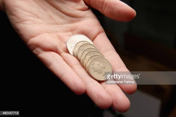 In this photo illustration a woman holds coins to the value of GBP 650 equivalent to the future UK minimum wage on May 20 2014 in Knutsford United...