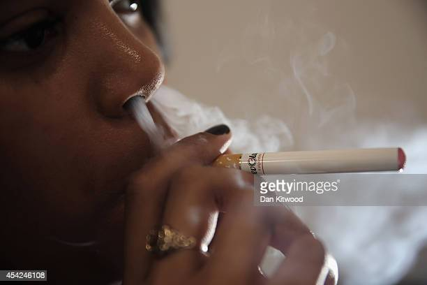 In this photo illustration a woman smokes an ECigarette at the VRevolution ECigarette shop in Covent Garden on August 27 2014 in London England The...