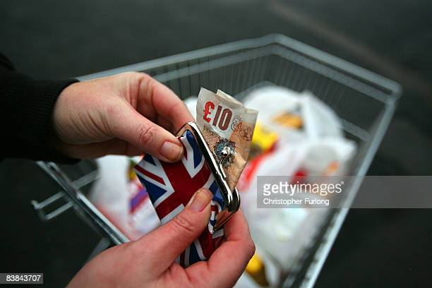 In this photo illustration a woman takes cash from her purse during shopping November 27 2008 in Manchester England With the Christmas shopping...