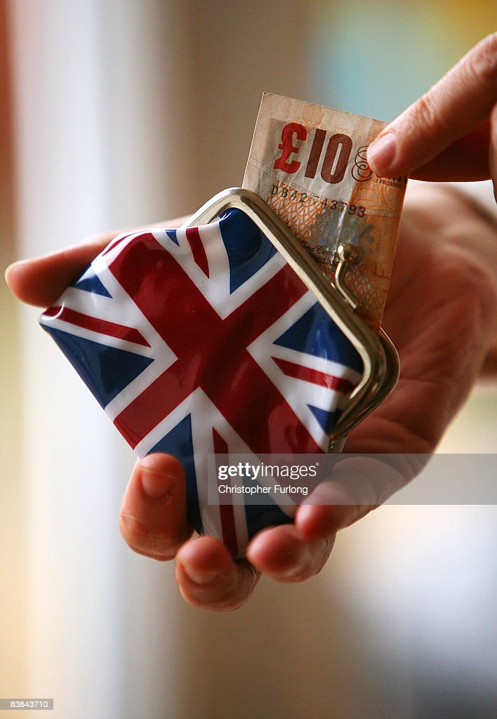 In this photo illustration a woman takes cash from her purse during shopping November 27, 2008 in Manchester, England. With the Christmas shopping season upon us many UK consumers are feeling the pinch as the financial crisis and economic downturn makes borrowing harder and more expensive.