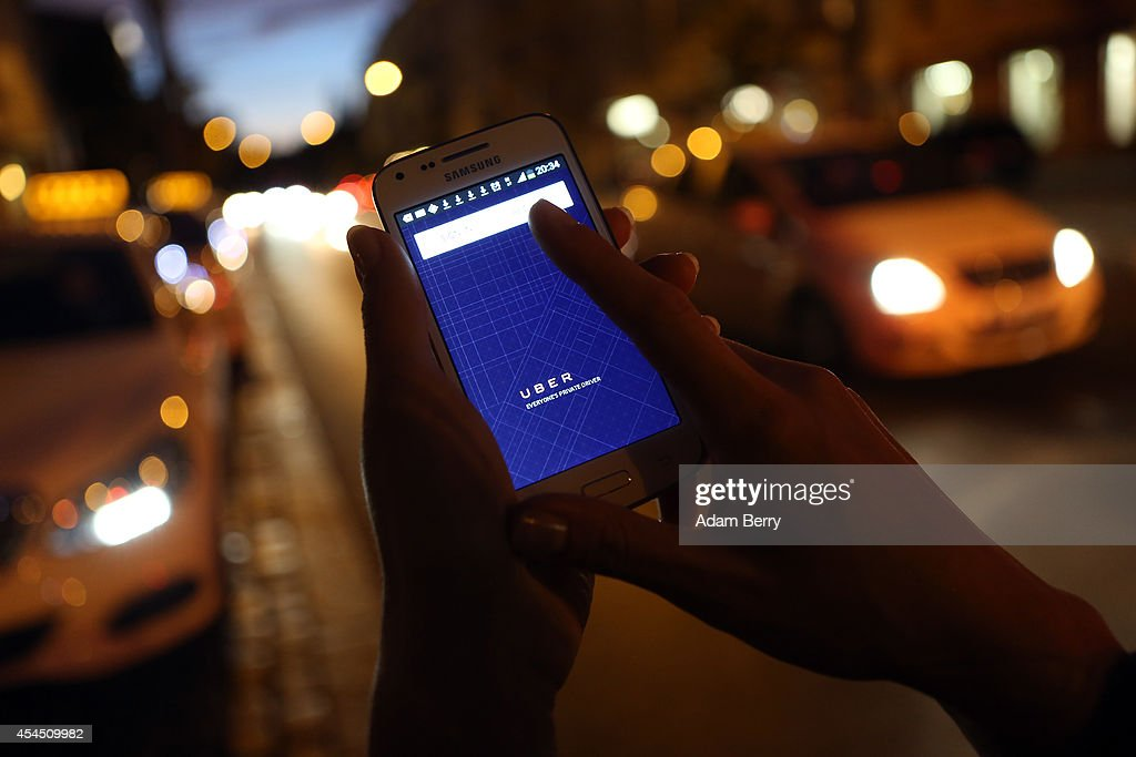 In this photo illustration a woman uses the Uber app on an Samsung smartphone on September 2 2014 in Berlin Germany Uber an app that allows passenger...