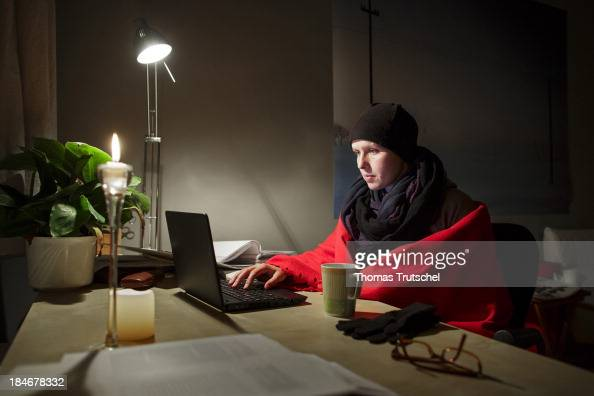 In this photo illustration a woman wearing a hat and wrapped in a blanket while working on a laptop at her desk at home in order to save heating...