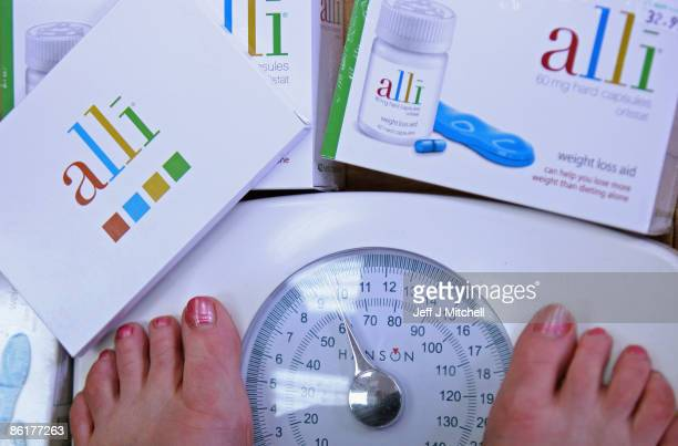 In this photo illustration a woman wighs herself at G W Allan chemists where the Alli slimming pill is stocked on April 23 2009 in Edinburgh Scotland...