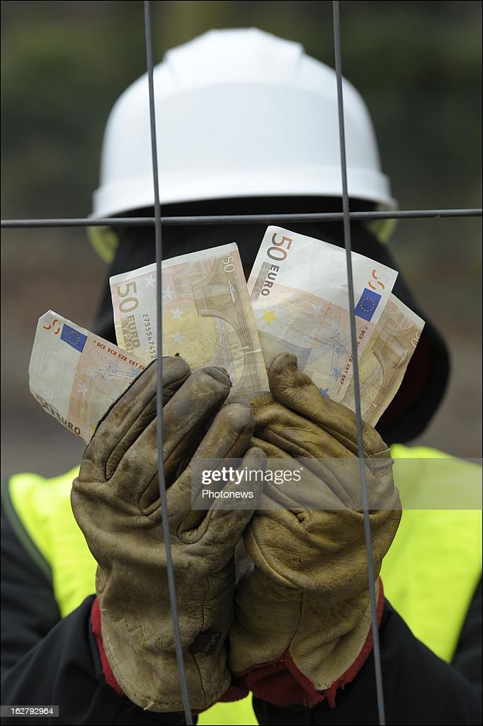 In this photo illustration, a worker holds a handful of Euros for reportedly undeclared work on February 27, 2013 in Brussels, Belgium. The European Commissioner is currently investigating methods to effectively fight against undeclared work.