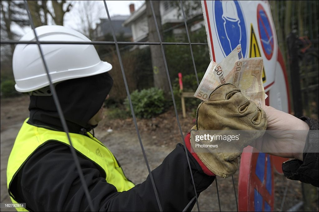 In this photo illustration, a worker is given Euros for reportedly undeclared work on February 27, 2013 in Brussels, Belgium. The European Commissioner is currently investigating methods to effectively fight against undeclared work.