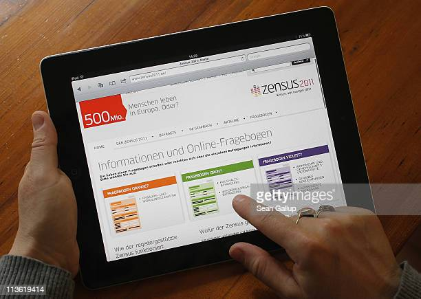 In this photo illustration a young woman scrolls through the website for the 2011 German national Census which has options for online form downloads...