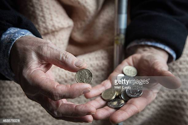 In this photo illustration an elderly person looks at cash at home on February 16 2015 near Bristol England The issues affecting the elderly along...
