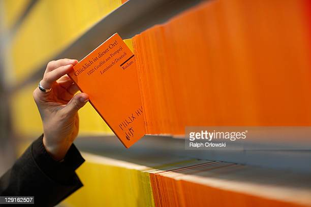 In this photo illustration an employee holds a book at the stand of German publisher Reclam during the Frankfurt Book Fair 2011 on October 13 2011 in...