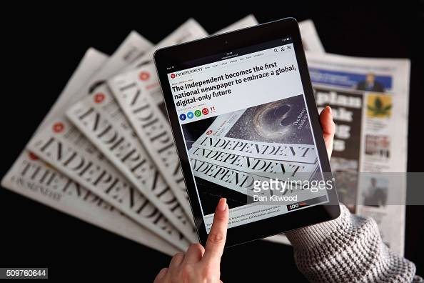 In this photo illustration an iPad is displayed with the Independent's online platform above a selection of the print versions of their titles on...