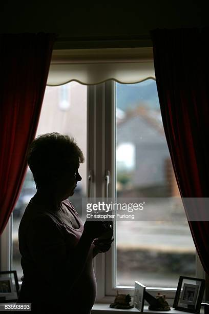 In this photo illustration an old age pensioner looks out of the window of her home on November 6 in Conwy Wales With the recent high rise in fuel...