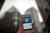 In this photo illustration communications from Twitter are displayed on a mobile device announcing the company's initial public offering and debut on...