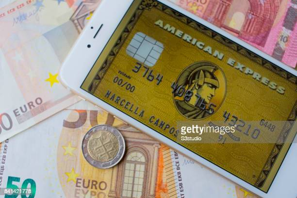 In this Photo Illustration Euro banknotes and coins with American Express card sample on an iPhone 6s Plus are arranged for a photograph on 30 August...