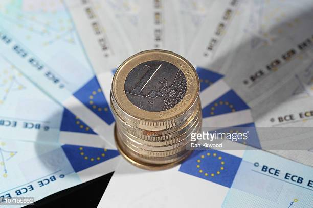 In this photo illustration Euro coins sit on 5 Euro notes on November 26 2010 in London England Concerns over the Euro zone debts have caused shares...