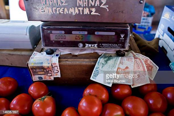 In this photo illustration euro notes and defunct drachma notes are displayed on a tomato stall by the stallholder on June 15 2012 in Athens Greece...