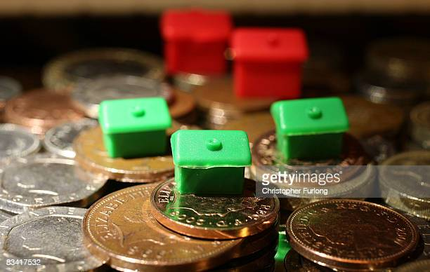 In this photo illustration houses from a Monopoly board game sit on top of British currency coins on October 24 2008 in Manchester England As markets...