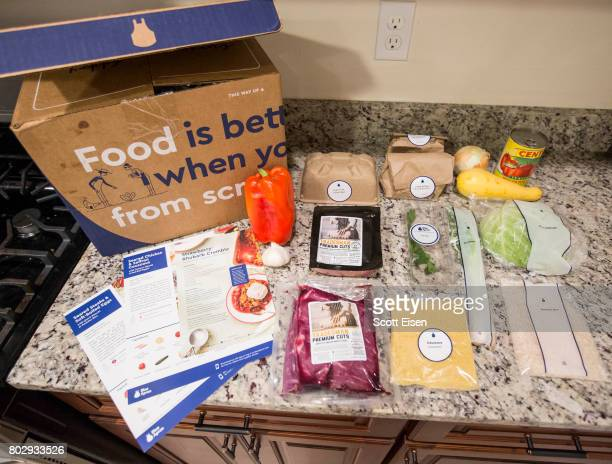 In this photo illustration items from a 'familyplan' Blue Apron box are displayed on a kitchen counter on June 28 2017 in Boston Massachusetts The...