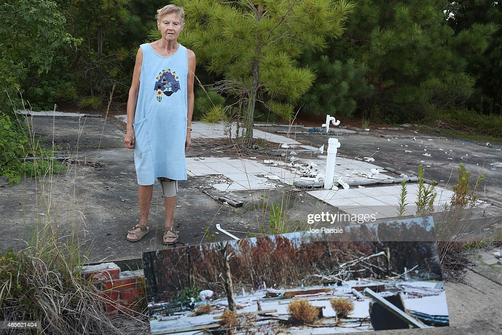 In this photo illustration Linda McLain stands on the slab of her former home August 28 2015 in Waveland Mississippi A neighbor holds up a photo that...
