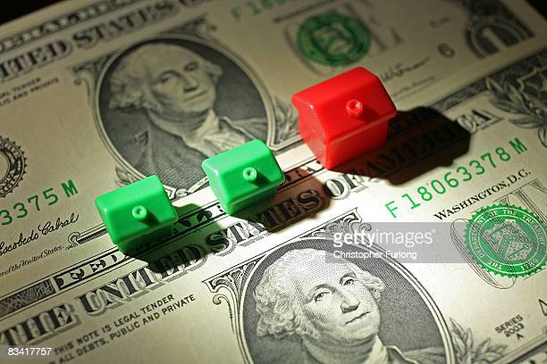 In this photo illustration miniature houses from a Monopoly board game can be seen next to American Dollar notes on October 24 2008 in Manchester...