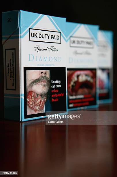 In this photo illustration mockup cigarette packets display some of the graphic picture warnings which will feature on packets in the future on...