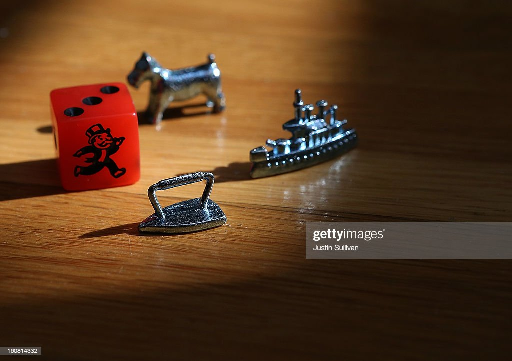 In this photo illustration, Monopoly board game pieces are displayed on February 6, 2013 in Fairfax, California. Toy maker Hasbro, Inc. announced today that fans of the board game Monopoly voted in an online contest to eliminate the iron playing figure and replace it with a cat figure. The cat gamepiece received 31 percent of the online votes to beat out four other contenders, a robot, diamond ring, helicopter and guitar.