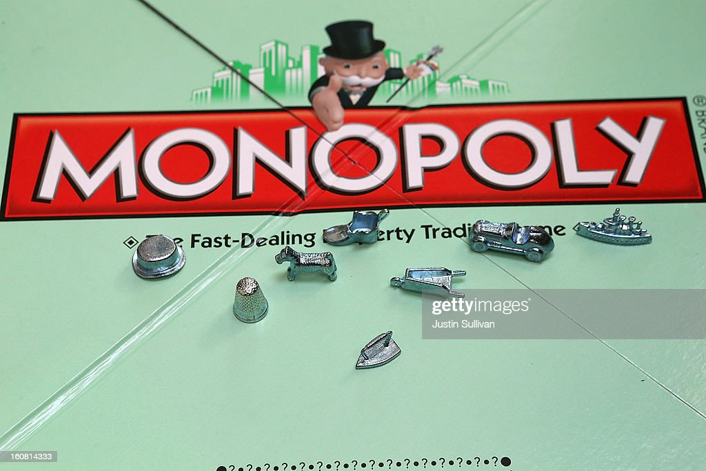 In this photo illustration, Monopoly game pieces are displayed on February 6, 2013 in Fairfax, California. Toy maker Hasbro, Inc. announced today that fans of the board game Monopoly voted in an online contest to eliminate the iron playing figure and replace it with a cat figure. The cat game piece received 31 percent of the online votes to beat out four other contenders, a robot, diamond ring, helicopter and guitar.