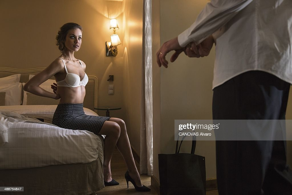 In this photo illustration of adultery, a couple on the bed of a hotel room on January 24, 2014 in France.