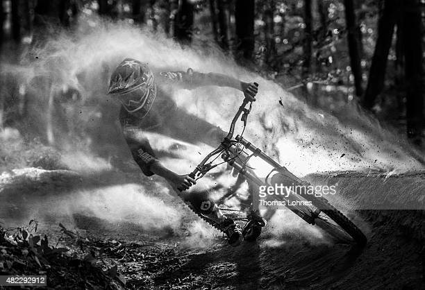 In this photo illustration people standing outside of the picture frame throw sand for dramatic effect behind a mountain biker illuminated by a...
