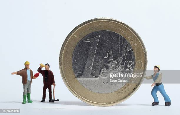 In this photo illustration plastic toy construction workers stand around a one Euro coin on December 15 2010 in Berlin Germany European leaders are...