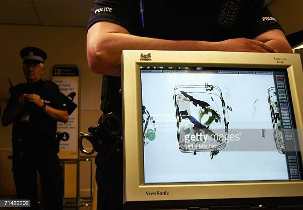 In this photo illustration police officers monitor knives in a bag passing through an xray machine at Glasgow Airport on July 12 2006 in Glasgow...