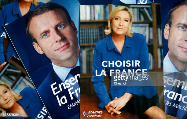 In this photo illustration posters with electoral programs of the president of the political movement 'En Marche Emmanuel Macron and President of the...