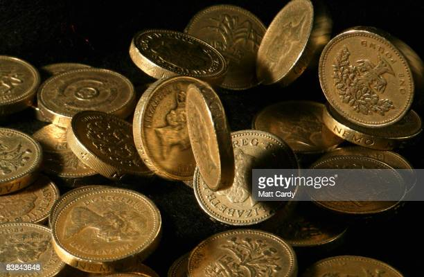 In this photo illustration pound coins drop in a pile on November 27 2008 in Bristol England Many UK consumers are feeling the pinch as the financial...