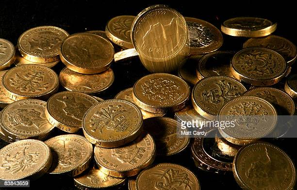 In this photo illustration pound coins drop into a pile on November 27 2008 in Bristol England Many UK consumers are feeling the pinch as the...