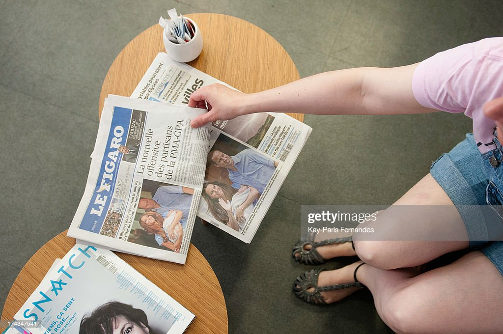 In this photo illustration, Prince William the Duke of Cambridge, and Catherine, the Duchess of Cambridge showing their new baby son at The Lindo Wing of St Mary's Hospital in London is covered in Le Figaro newspaper as a woman reaches to a copy of the paper on July 24, 2013 in Paris, France. The Duchess of Cambridge gave birth to a boy on July 22 at 16.24 BST with Prince William at her side.