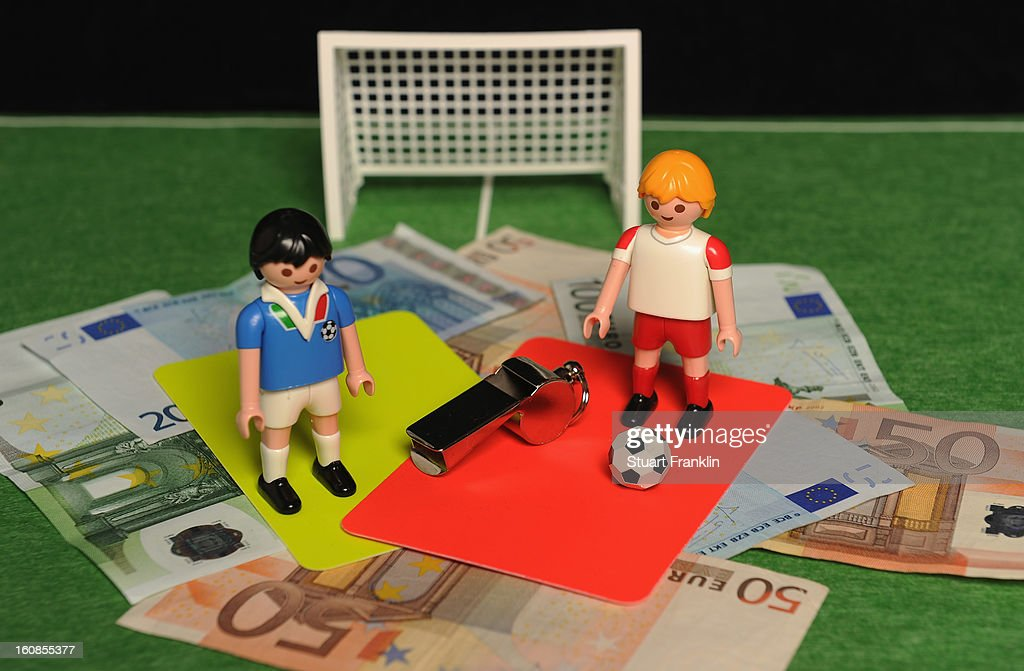 In this photo illustration, referee's red and yellow cards along with a whistle, Euro bank notes and a table soccer game are juxtaposed on February 6, 2013 in Hamburg, Germany. Europol have uncovered evidence that hundreds of football matches were subject to corruption leaving more than 400 officials and players under suspicion of involvement.