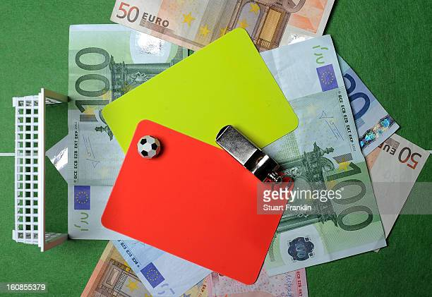 In this photo illustration referee's red and yellow cards along with a whistle Euro bank notes and a table soccer game are juxtaposed on February 6...